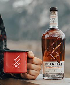 Man drinking Bearface whisky in a mug